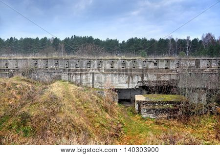 Old military fort near Grodno, Belarus. Horizontal concrete wall with rectangular battlements surrounded by hills and forest.