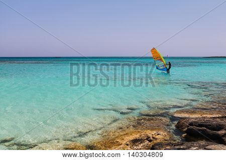 Elafonisi, Island Crete, Greece, - June 26, 2016: The windsurfers is moving in the Libyan Sea ( part of the Mediterranean Sea) on the beautiful beach of Elafonisi with pink sand.beautiful beach of Elafonisi with pink sand.