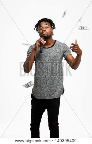 Young handsome african man looking at camera, winking, singing in microphone over white background. Copy space.
