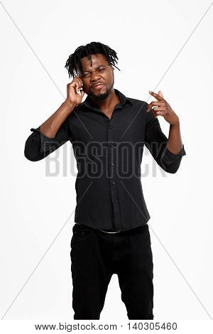 Young successful african businessman in black shirt speaking on phone, smiling over white background.