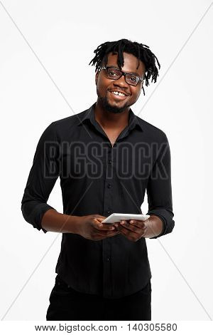 Young successful african businessman in black shirt and glasses looking at camera, holding tablet, smiling over white background.