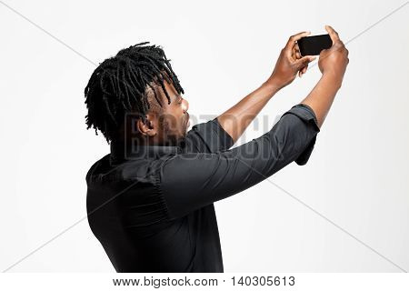 Young successful african businessman in black shirt making selfie over white background. Copy space.
