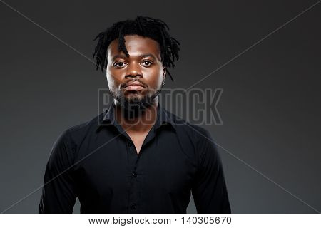 Young successful african businessman in black shirt posing, looking at camera over dark background. Copy space.