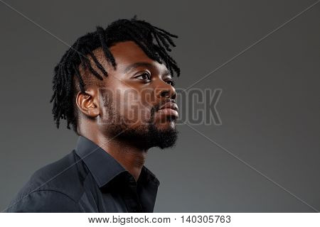 Young successful african businessman in black shirt posing, thinking over dark background. Copy space.