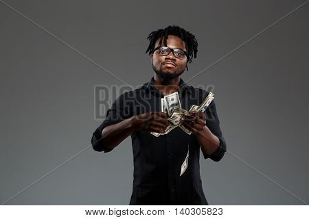 Young successful african businessman in black shirt and glasses throwing money, looking at camera over dark background. Copy space.