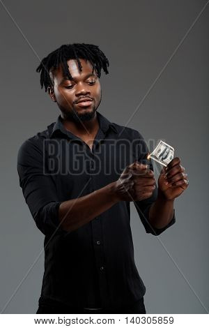 Young successful african businessman in black shirt burning money, grining over dark background.