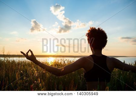 Silhouette of young beautiful sportive girl practicing yoga in field at sunrise.