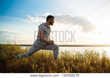 Young handsome sportive man training in field at sunrise.