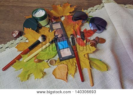 Cosmetics sunglasses autumn leaves on a wooden table