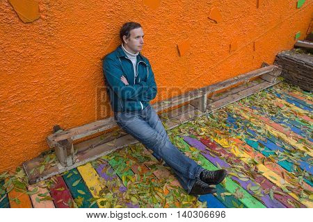 Sad man sitting on a bench among fallen leaves. People