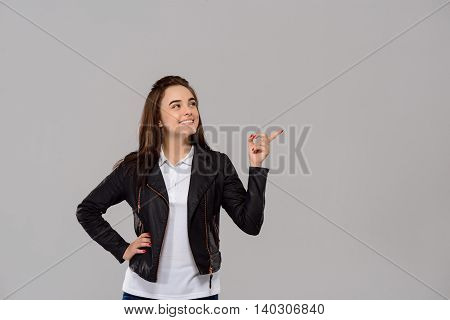 Young beautiful girl pointing finger in side, smiling over purple background. Copy space.
