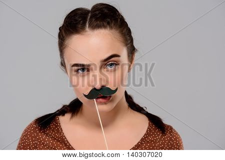 Young beautiful girl wearing fake mustache, looking at camera over purple background. Copy space.