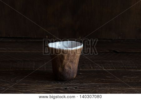 brown and white clay cup ceramic glass handmade pottery on a brown background.