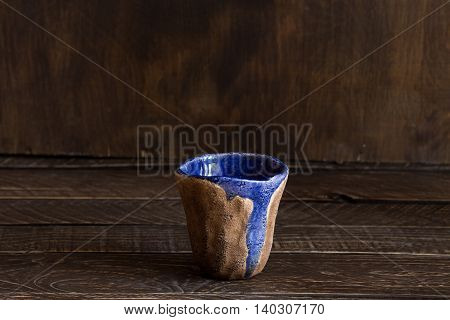 ceramic glass handmade brown-blue clay cup pottery on a brown background.
