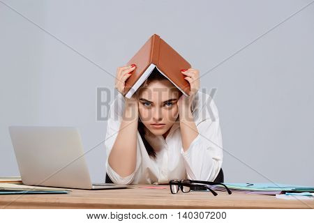 Tired young beautiful businesswoman sitting at workplace, looking to camera over purple background. Copy space.