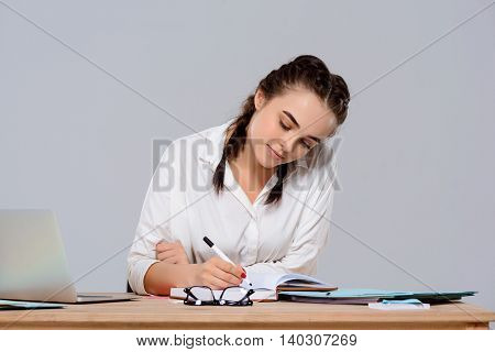 Young beautiful businesswoman in glasses sitting at workplace, writing, smiling over purple background. Copy space.