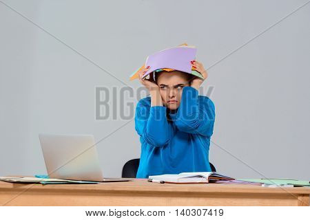 Displeased young beautiful businesswoman sitting at workplace, holding colorful folders over purple background. Copy space.