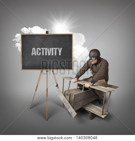 Activity text on blackboard with businessman and wooden aeroplane