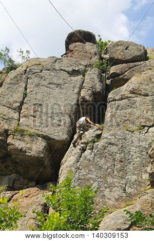 Man climber climbing up on a rock