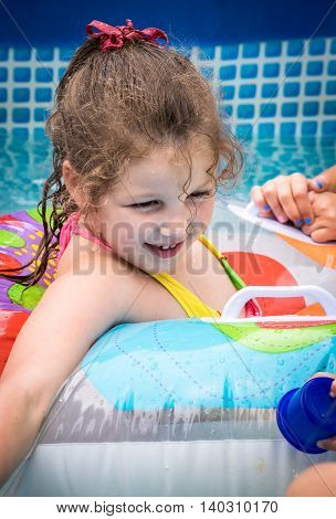 Smiling girl swims in pool in circle