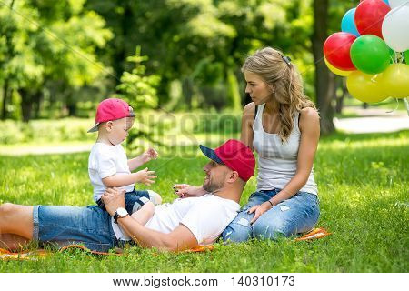 Little boy with mom and dad playing in the park. Happy family walking in the park. Funny mom dad and baby playing in the park in the summer.