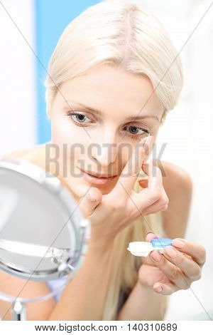 The woman assumes contact lenses. Inserting contact lenses.