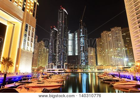 DUBAI UAE - SEPTEMBER 11: The night illumination of Dubai Marina on September 11 2013 in Dubai UAE. It is an artificial canal city built along a two mile (3 km) stretch of Persian Gulf shoreline.