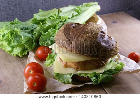 Picnic, sandwich with meat, cheese and fresh vegetables is lying on a rustic wooden table