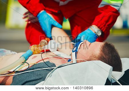 Paramedic preparing the patient after resuscitation for transport to the hospital.