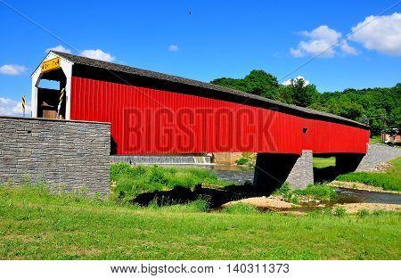 Asheville Pennsylvania - June 6 2015: 1884 vernacular Burr arch-truss wooden covered bridge over the Octoraro Creek *