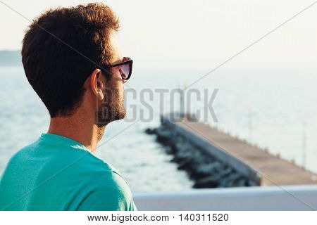 Young man looking at sunset standing on the dock
