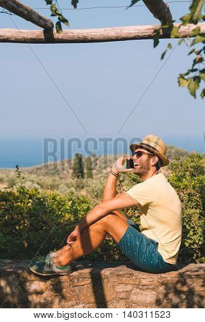 Young man sitting on balcony and talking on the smartphone, seaside landscape
