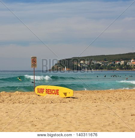 Popular beach in Sydney. Livesaving surfboard on the shore.
