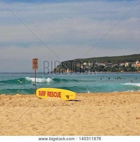 Popular beach in Sydney. Livesaving surfboard on the shore.