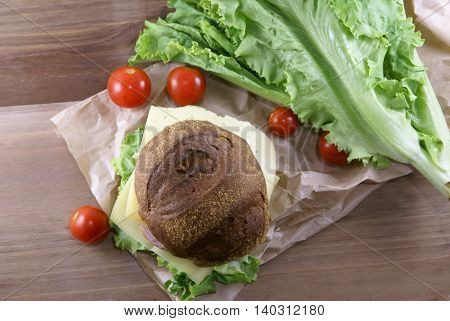 Picnic, sandwich with meat, cheese and fresh vegetables is lying on a rustic wooden table. Top view