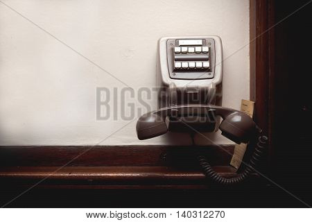 Old-button phone on a white wall. Tinted photo. Empty place. Blank space