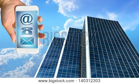 business building against beautiful blue sky and clouds with hand holding smartphone contact concept