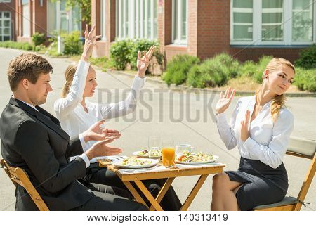 Group Of Three Young Businesspeople Having Argument In Restaurant