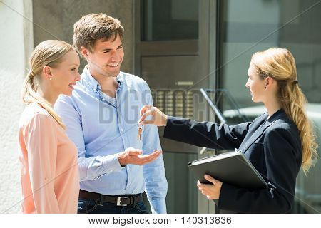 Female Estate Agent Giving House Key To Young Happy Couple