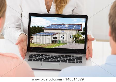Close-up Of Estate Agent Showing House On Laptop To Couple