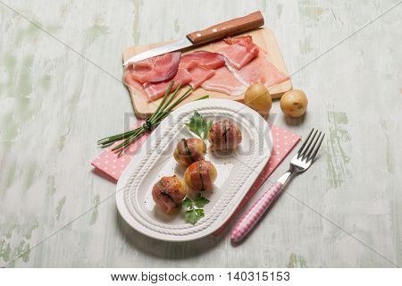 pork rolled up with potatoes on a plate