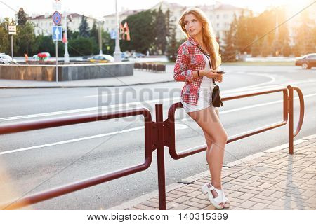 Young woman using a smartphone while standing by the fence on the street and listen the music