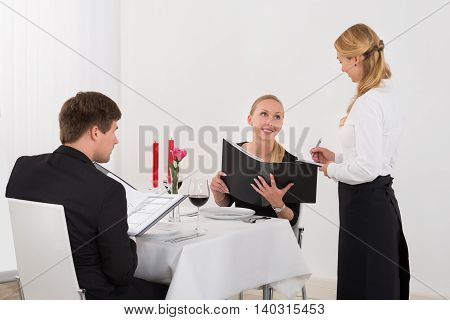 Female Waitress Taking An Order From A Happy Couple In Restaurant