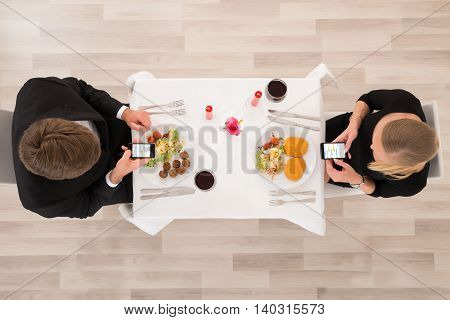 High Angle View Of Couple Looking At Their Mobile Phones In Restaurant