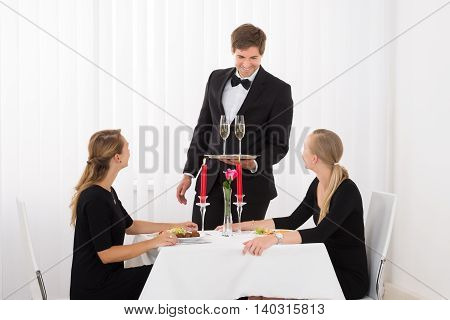 Happy Waiter Serving Glass Of Champagne To Female Friends In Restaurant With Food On Table