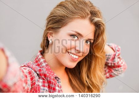 Girl makes selfie photo. Close up portrait view of the camera