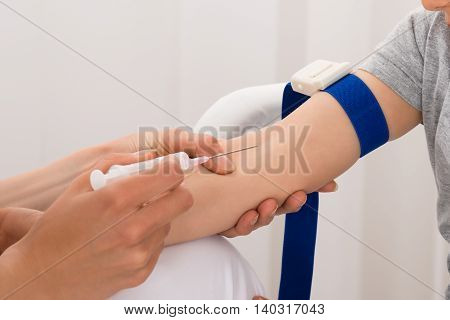 Close-up Of Doctor Taking Blood Sample In Clinic