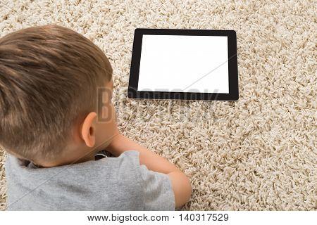 Close-up Of Boy Looking At Blank Digital Tablet