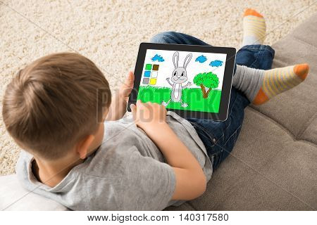 High Angle View Of Cute Little Child Playing Game On Digital Tablet