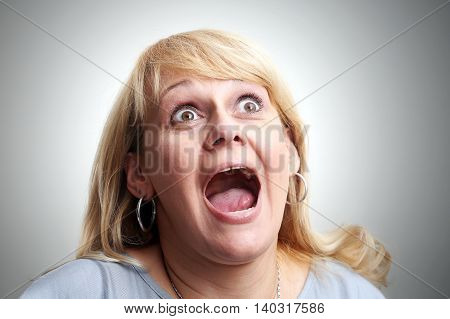 Shocked and scream woman on a gray